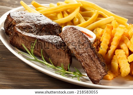 Grilled steaks, chips and vegetables