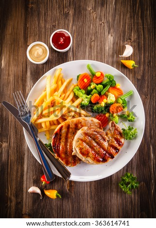 Grilled steaks, French fries and vegetable salad  - stock photo