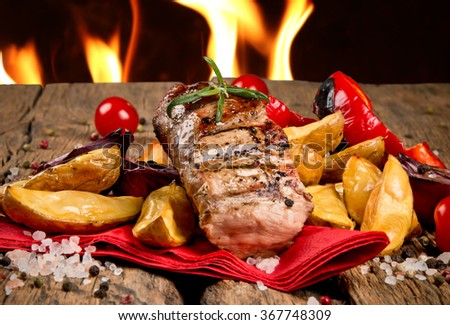 Grilled steaks on wooden table  - stock photo