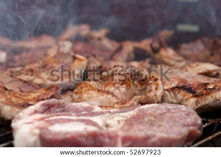 Grilled steaks rest on a barbecue grill