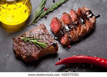 Grilled striploin sliced steak over stone table - stock photo