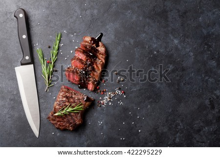 Grilled striploin sliced steak with salt and pepper and knife over stone table. Top view with copy space - stock photo