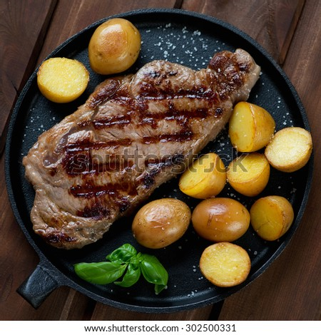Grilled striploin steak with potato in a frying pan, top view