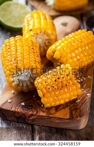 Grilled sweet corn with salt and lime on wooden table - stock photo