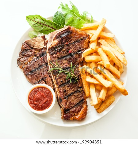 Grilled t-bone or porterhouse steak seasoned with rosemary and served with golden French fries, fresh leafy herb salad and a tomato dip, high angle view on white