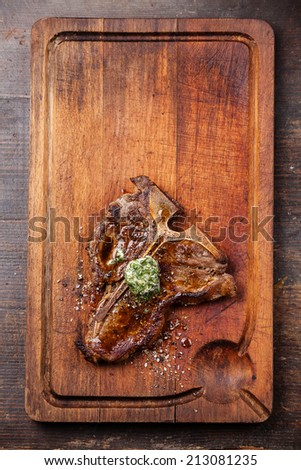 Grilled T-Bone Steak and herbs butter on meat cutting board - stock photo