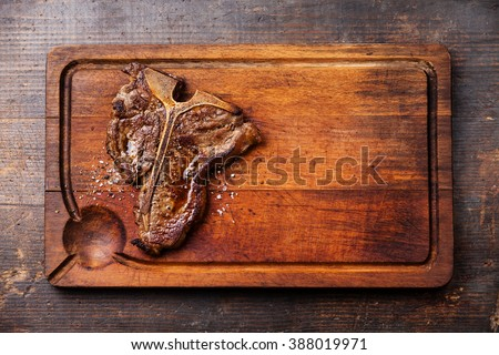 Grilled T-Bone Steak on cutting board on dark wooden background - stock photo