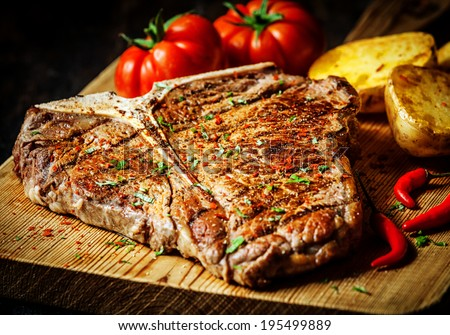 Grilled T-bone steak seasoned with spices and fresh herbs served on a wooden board with fresh tomato , roast potatoes and red hot chili peppers - stock photo