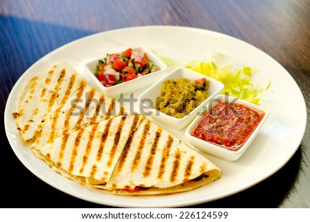 Grilled taco or tortilla with a savory filling served with salsa and a variety of dipping sauces on a plate - stock photo