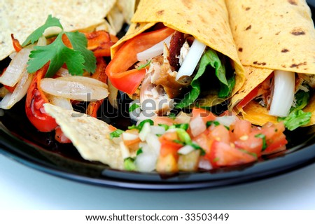Grilled teriyaki chicken, red bell pepper, white onion, cilantro and romain lettuce are used to fill the tomato and basil wraps with grilled veggies and fresh tomato salsa and chips on the plate - stock photo