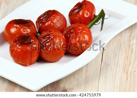 Grilled tomatoes. Bunch of tomatoes. Tomatoes on the plate. Ripe tomatoes. Barbecue vegetable.  - stock photo