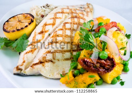 Grilled Trout and Butternut Squash: Gourmet barbecued grilled trout with grill marks and a side vegetable salsa and rice on a white plate. - stock photo