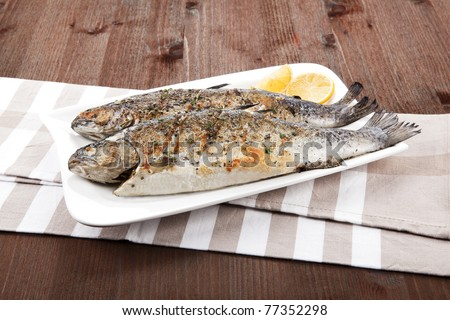 Grilled trout on white plate with lemon pieces on kitchen towel on wooden table. - stock photo