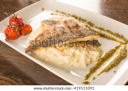 Grilled trout with risotto, tomatoes, and pesto sauce