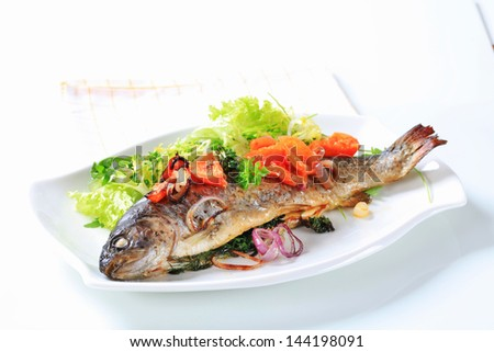 Grilled trout with vegetables and lettuce salad on an oval plate - stock photo