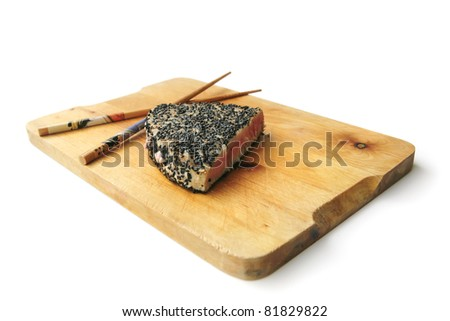 grilled tuna piece with black sesame on wooden plate and wooden chopsticks isolated on white - stock photo