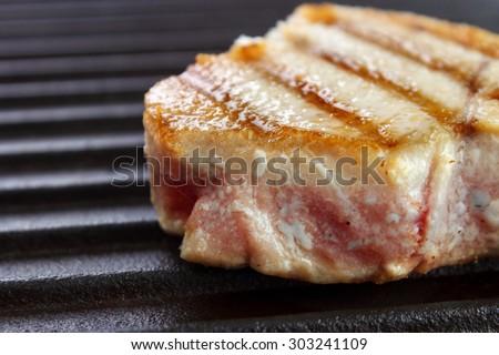 Grilled tuna steak on black cast iron griddle closeup - stock photo