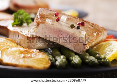 Grilled tuna steak served on asparagus with roasted potatoes on a black plate. - stock photo