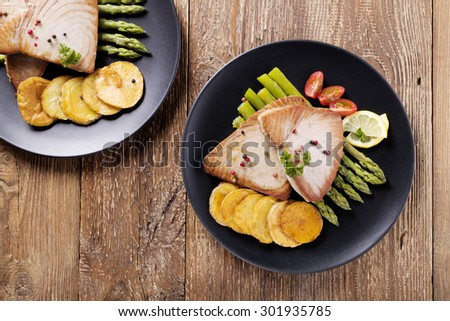 Grilled tuna steak served on asparagus with roasted zmieniakami on a black plate.