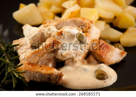 Grilled turkey meat with cheese sauce and capers on a black plate with potato and branch of rosemary - stock photo