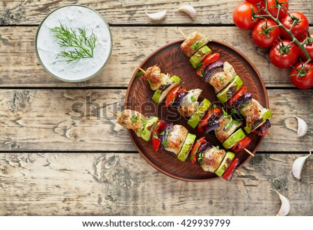 Grilled turkey or chicken meat shish kebab skewers with tzatziki sauce, chopped parsley, garlic and tomatoes on rustic wooden table background. Traditional barbecue grill food - stock photo