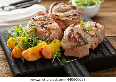 Grilled turkey tenderloins wrapped with bacon served with fresh peaches - stock photo
