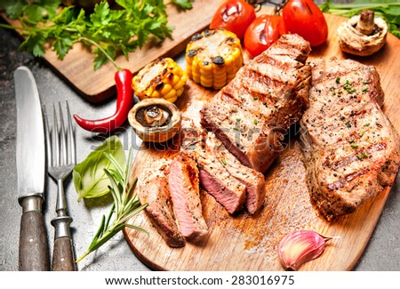 Grilled veal steaks with vegetables on cutting board - stock photo