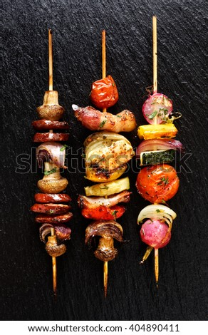 Grilled vegetable and meat skewers  on the black stone background - stock photo