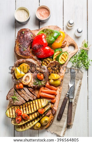 Grilled vegetables and steak with salt on wooden board - stock photo