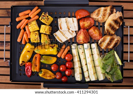 Grilled vegetables, bread and cheese on a grilling pan - stock photo