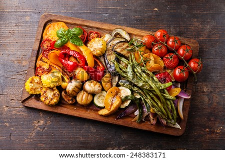 Grilled vegetables on cutting board on dark wooden background - stock photo