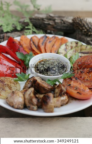 Grilled vegetables on the white plate. grilled vegetbles on the wooden background. Grilled onion. Grilled tomato. Grilled pepper. grilled mushrooms. Grilled vegetable marrow. Grilled healthy food. - stock photo