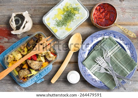 Grilled vegetables with eggplant, tzatziki, Turkish cacik with dill, and hot red chili pepper paste ready to be served with plates and cutlery on an old weathered wooden table - stock photo