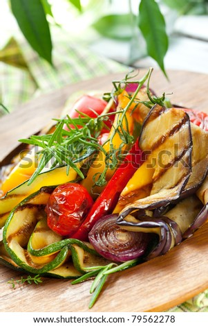 Grilled vegetables with rosemary and thyme on the wooden plate - stock photo