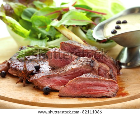 Grilled venison with fresh vegetables on wood plate. - stock photo