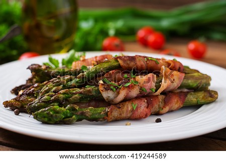 Grilled violet asparagus wrapped with bacon - stock photo