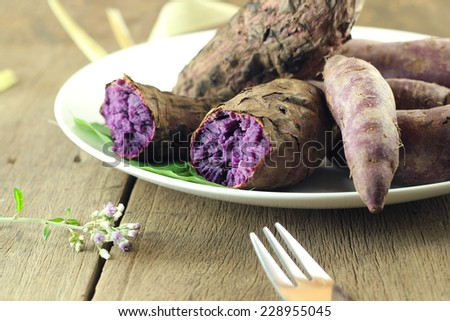 Grilled violet potato on vintage wood table.