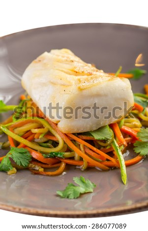 Grilled white fish fillet with a colorful salad isolated on white background - stock photo