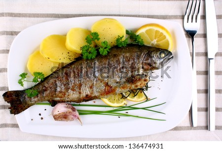stock-photo-grilled-whole-trout-with-potato-lemon-and-garlic-top-view ...