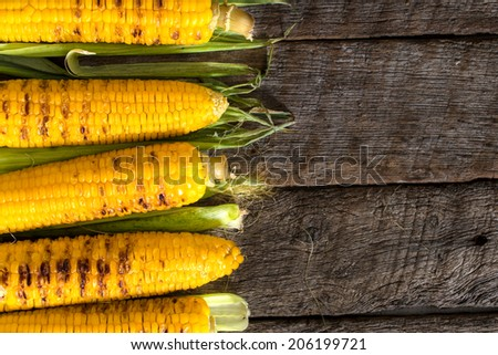 Grilled young corn on the wooden background with blank space on right side  - stock photo