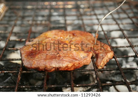 Grilling a steak on the barbeque with a fork