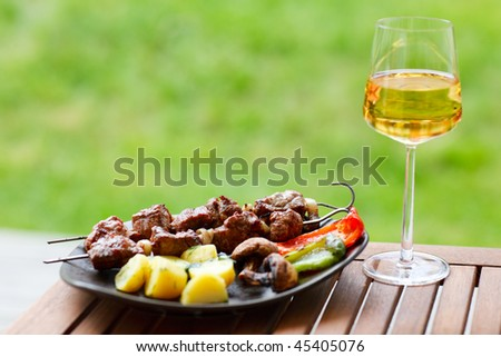Grilling at summer weekend. Fresh grilled meat and vegetables served outdoors.