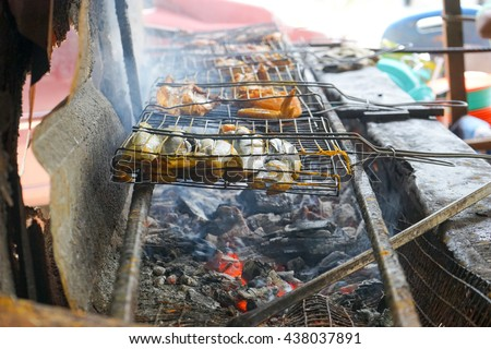 Grilling fish and chicken on flame - stock photo