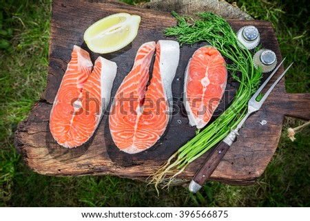 Grilling fresh salmon with dill and lemon - stock photo