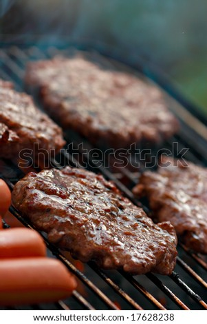 Grilling hamburgers and hot dogs - stock photo