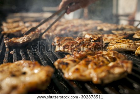 Grilling  meat with barbecue stuff. Horizontal shot - stock photo