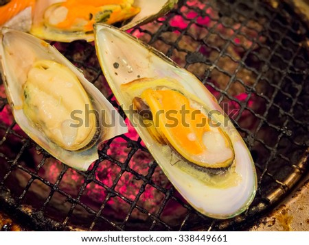 Grilling mussels on charcoal stove - stock photo
