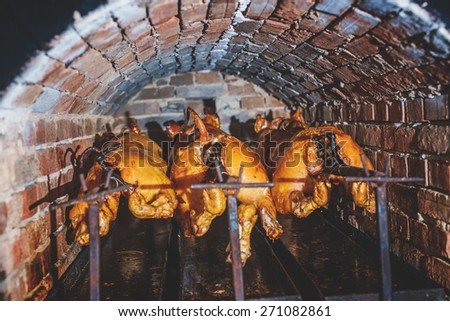 Grilling pig in a hot brick oven.  - stock photo
