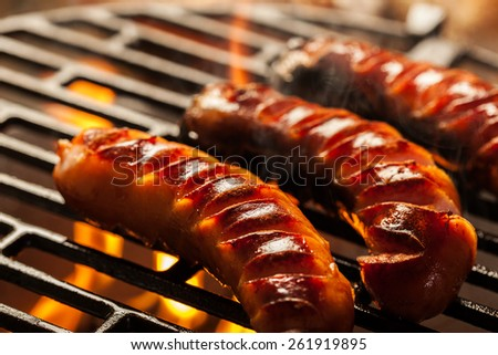 Grilling sausages on barbecue grill. Selective focus - stock photo