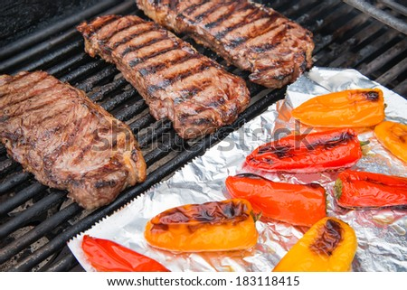 Grilling steaks and colorful peppers on foil - stock photo